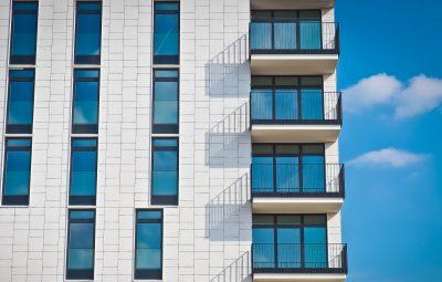 Immeuble neuf blanc avec des balcons et des grandes fenêtres
