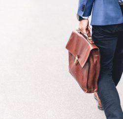 Homme de dos avec malette en cuir, se rendant au travail dans une entreprise