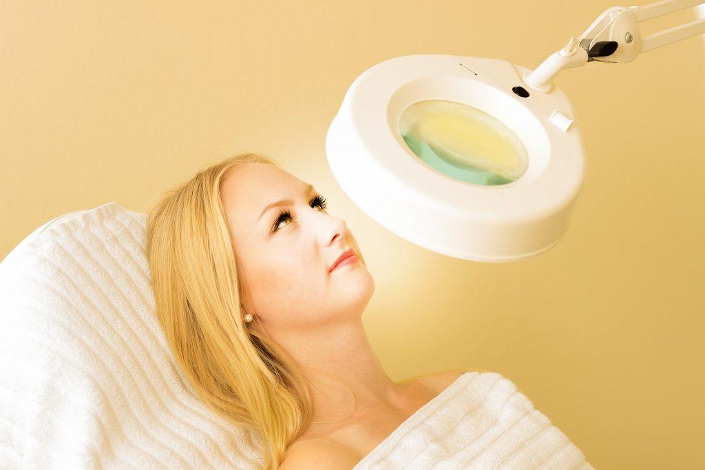 Jeune femme allongée sur un siège sous une lampe grossissante