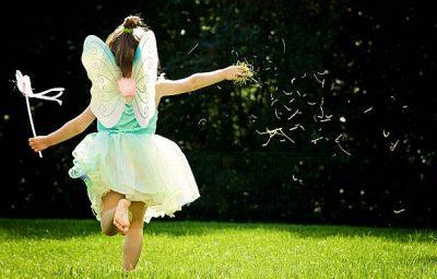 Une fillette déguisée en fée qui court dans le jardin
