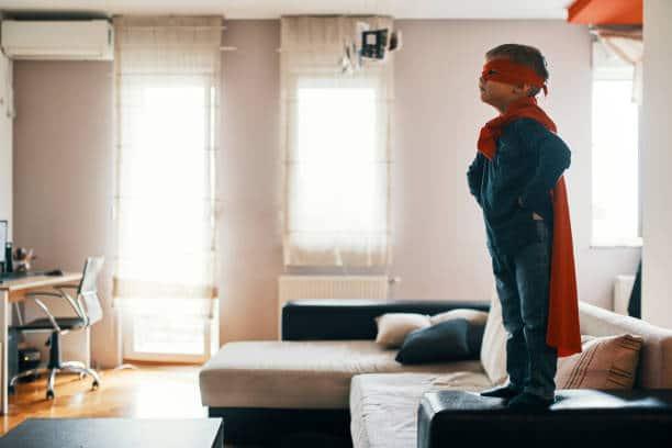 Petit garçon déguisé en super-héros, debout sur le canapé
