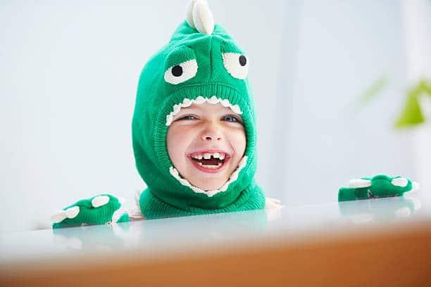 Gros plan sur le visage d'un enfant déguisé en dinosaure