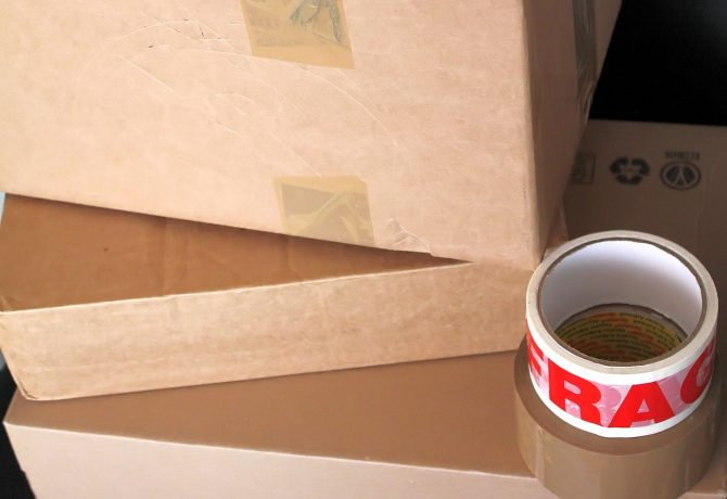 Cartons de déménagement empilés avec des rouleaux de scotch posés au-dessus