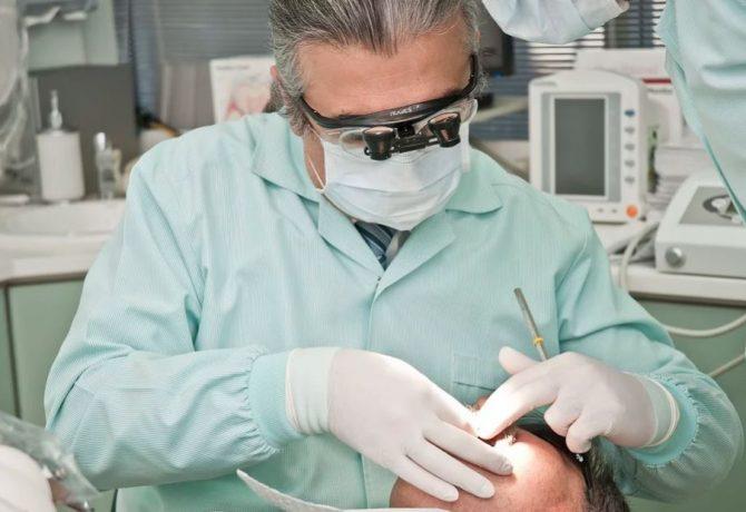 Dentiste qui effectue des soins dentaires sur une patiente