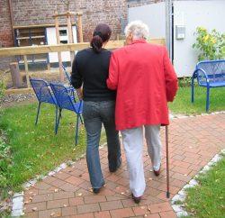résident de maison de retraite en promenade avec un soignant